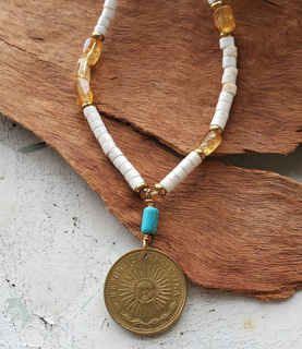 White, turquoise, yellow gemstone Argentina coin necklace on wood