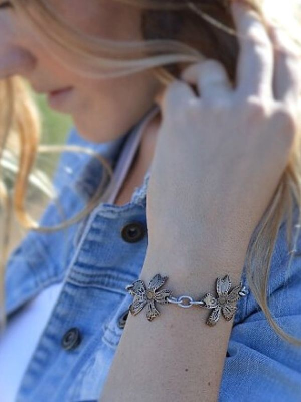 triple metal wildflower bracelet on arm