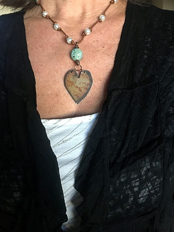 wearing black jacket and big rustic heart statement necklace