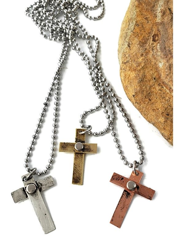 three handcrafted riveted mixed metal crosses necklaces  on rock