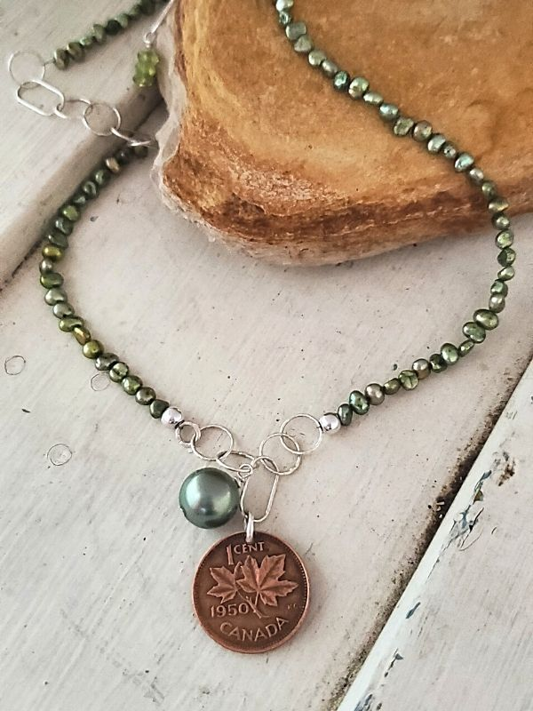 Green pearl Canada coin necklace on wood
