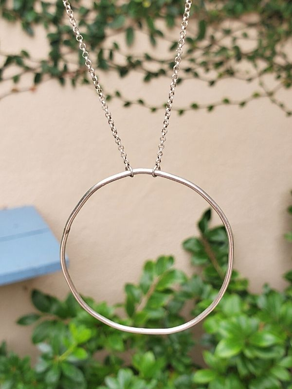 silver circle necklace hanging in the garden