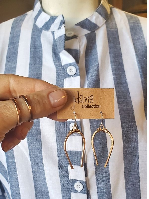 holding horseshoe earrings with thumb rings against a striped outfit