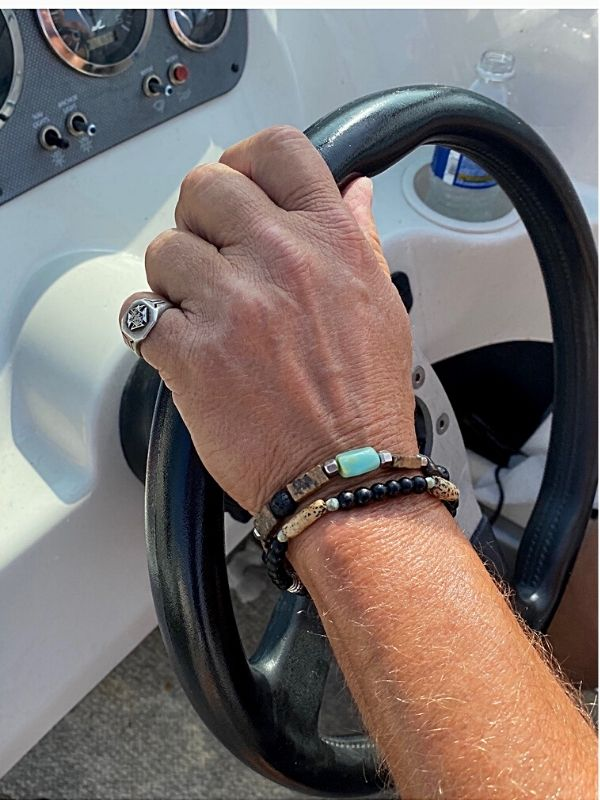 guy with bracelets on arm while driving a boat