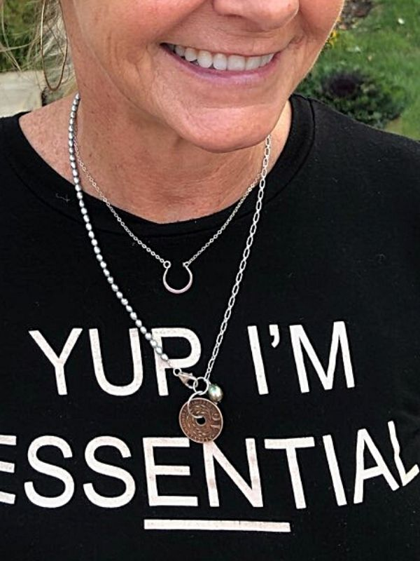 female with black tee shirt and old coin necklace